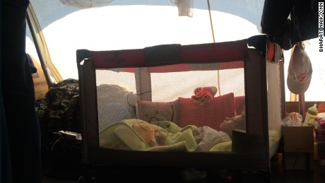 Alyaman Daar, aged six and dying of muscular dystrophy, lies in a cot at the Eko refugee camp close to the Greece-Macedonia border.
