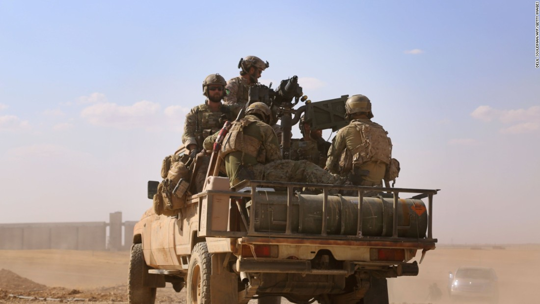 In the back of a pickup truck in the village of Fatisah in the northern Syrian province of Raqqa, armed men in uniform identified by Syrian Democratic Forces as U.S. special operations forces ride on May 25, 2016.