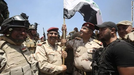 Iraqi forces celebrate the recapture of the town of Karma from ISIS.