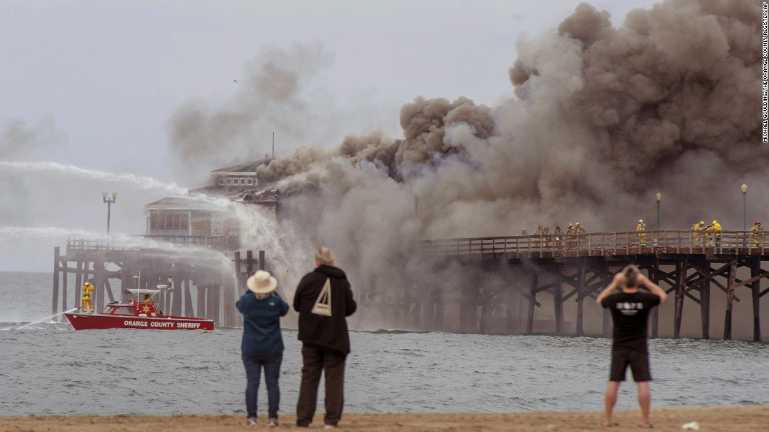 People watch firefighters battle a blaze on a pier in Seal Beach, California, on Friday, May 20.