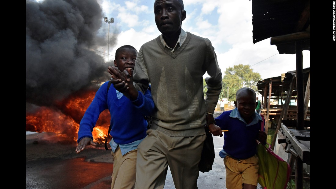 A man leads schoolchildren away from tear gas and a burning barricade during a demonstration in Nairobi, Kenya, on Monday, May 23. Opposition supporters were demanding a change of leadership at the electoral commission.