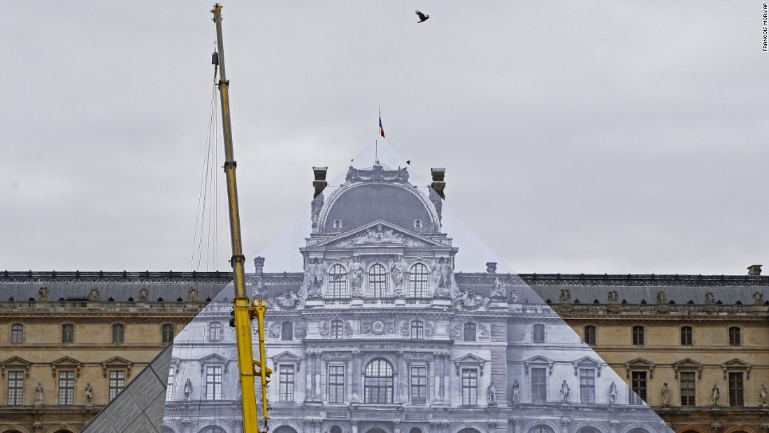 "A giant picture is pasted onto the Louvre Pyramid as part of an art installation in Paris on Tuesday, May 24. <a href=""http://www.cnn.com/2016/05/24/arts/jr-louvre/"" target=""_blank"">The illusion,</a> by street artist JR, made it look as though the pyramid had disappeared."