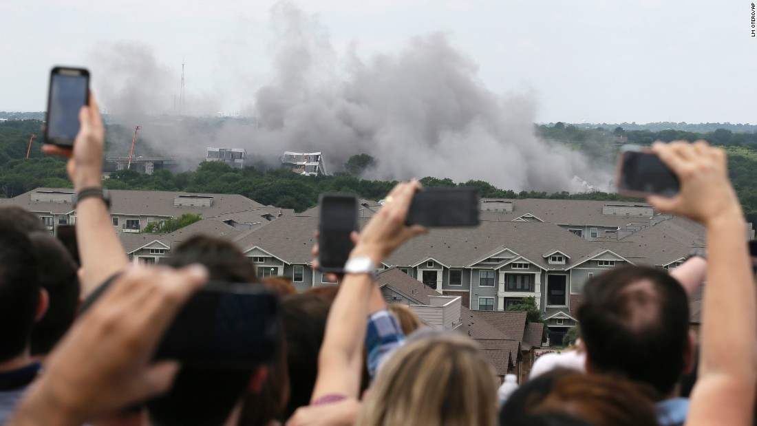 American Airlines employees watch as the company's former headquarters is imploded in Fort Worth, Texas, on Friday, May 20.