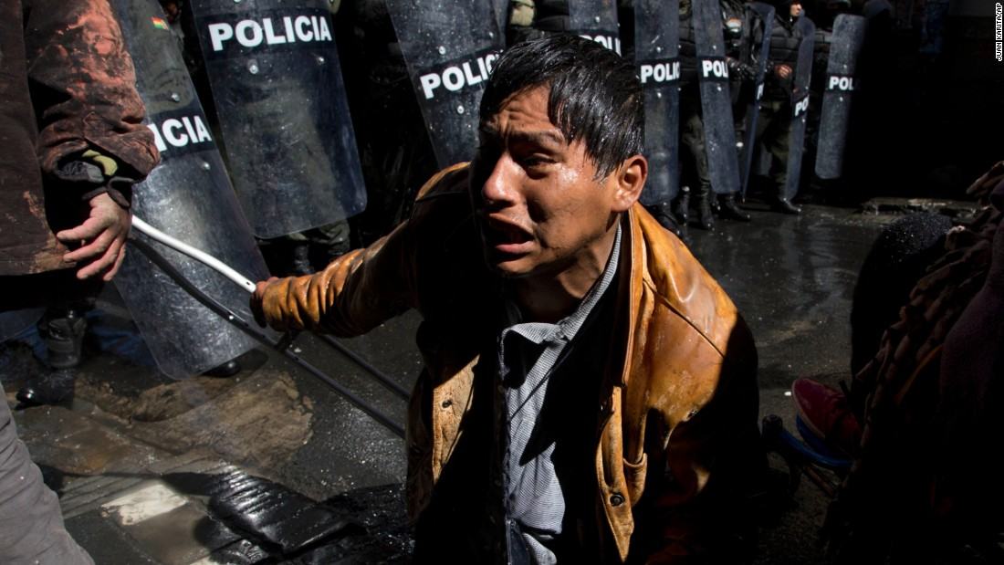 A disabled protester, on his knees and holding a crutch, confronts police blocking him from reaching the National Palace in La Paz, Bolivia, on Wednesday, May 25. Demonstrators were demanding larger state benefits for people with disabilities.