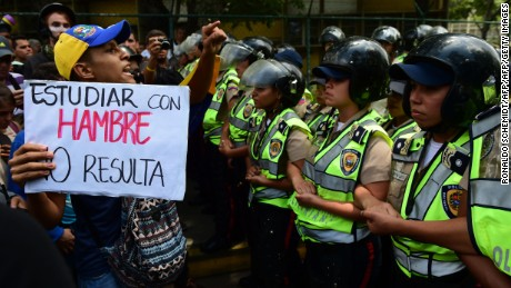 "A protester holds a sign reading ""studying when you're hungry doesn't work"", as police stand guard while public university students in Venezuela protest the policies of the government of President Nicolas Maduro in Caracas on May 26, 2016. / AFP / RONALDO SCHEMIDT        (Photo credit should read RONALDO SCHEMIDT/AFP/Getty Images)"