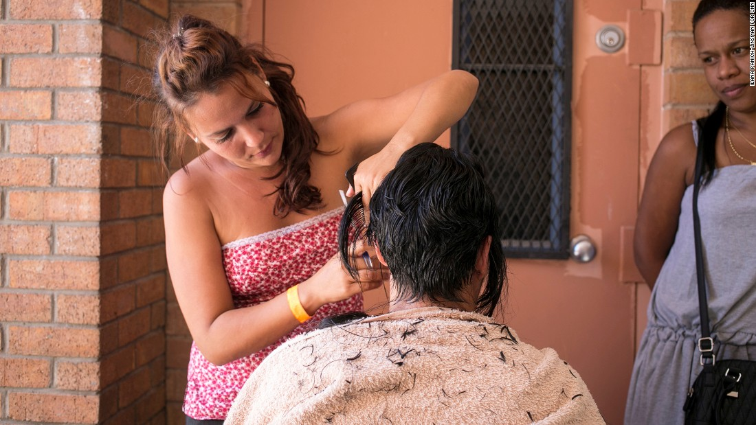"Lisandra Martinez Machado, 27, sets up a makeshift salon at the center to help Yusime Pena Gonzalez, 45, keep a promise she made to a saint on her long journey to the United States: If she made it across the U.S.-Mexico border, she'd get her hair cut. ""It's a new country, a new life,"" Pena says. ""The light has changed."""