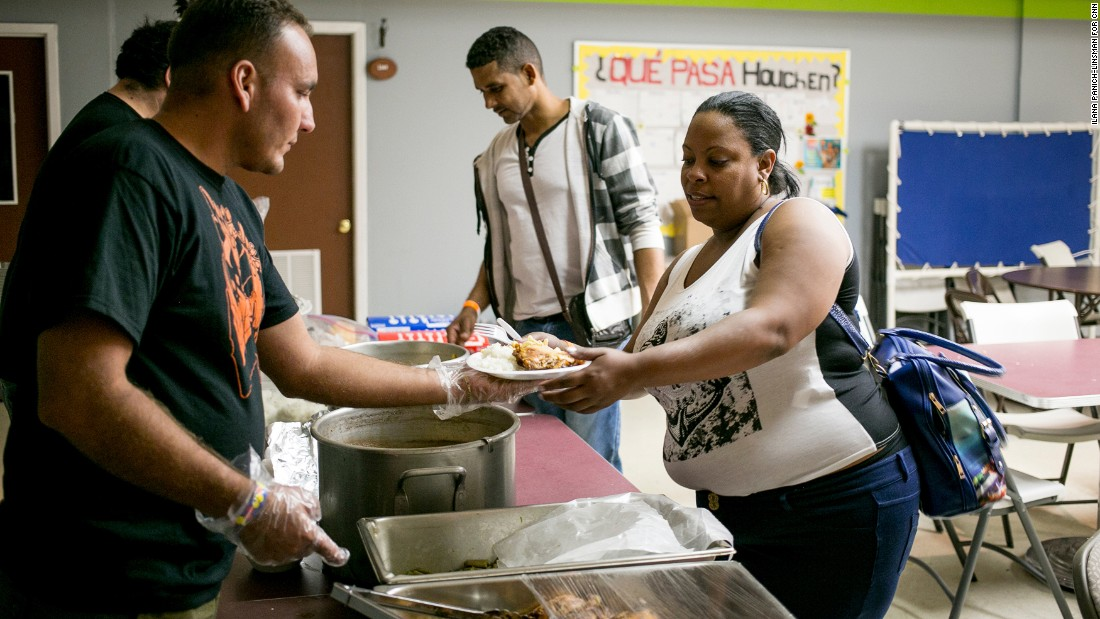 """No matter what time the new immigrants arrive, Julio Rojas Rubio and other volunteers serve them a meal. Rojas, who crossed the border earlier in May, says he loves seeing the looks on his fellow Cubans' faces. """"I feel good knowing that they have also achieved their dream of coming to the United States,"""" he says."""