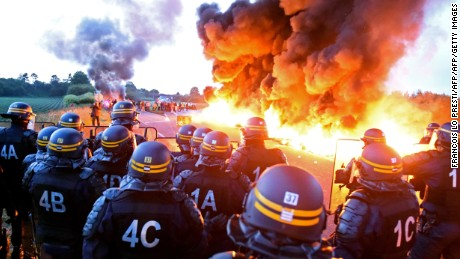 Riot police stand guard as workers at an oil refinery burn tires and blockade an oil depot in Douchy-Les-Mines, France, on May 25 to protest proposed changes to labor laws.