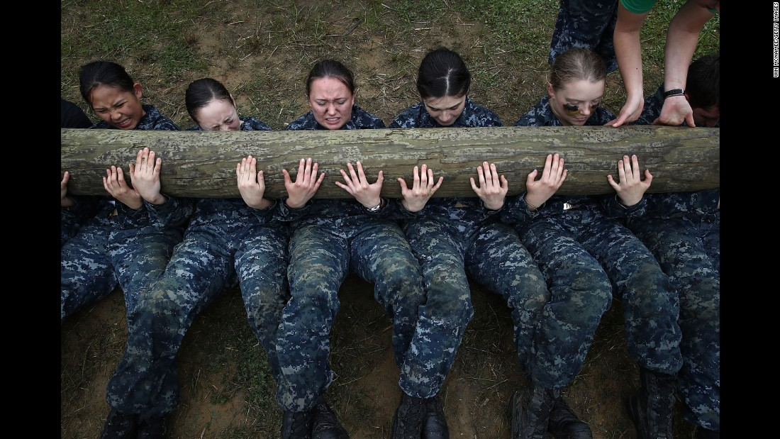 Plebes from the U.S. Naval Academy perform situps with a 12-foot log on top of them during the annual Sea Trials training exercise on Tuesday, May 17.