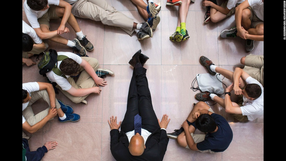 U.S. Sen. Cory Booker sits on the floor with eighth-graders visiting the Hart Senate Office Building in Washington on Tuesday, May 24.