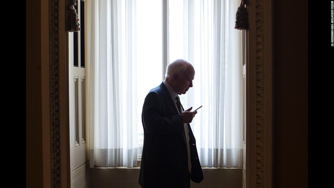 U.S. Sen. John McCain talks on his phone as he steps off the Senate floor in Washington on Wednesday, May 25.