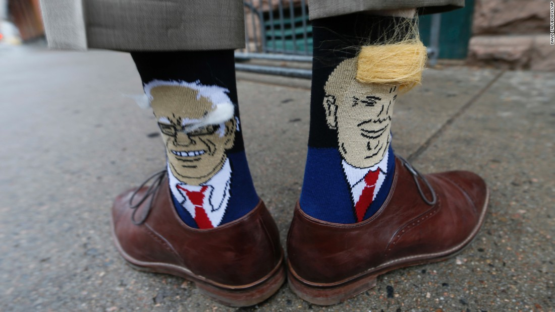 Colorado Gov. John Hickenlooper shows off his socks -- one with Democratic presidential candidate Bernie Sanders, left, and the other with Republican candidate Donald Trump -- before signing copies of his autobiography in Denver on Thursday, May 26.