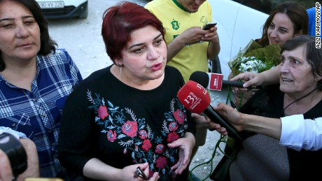 Azeri Khadija Ismayilova, center, a reporter for Radio Free Europe/Radio Liberty, who has become a symbol of defiance, praised by human rights and free-speech organizations around the world, speaks to journalists right after she has been released in Baku, Azerbaijan, Wednesday, May 25, 2016. A prominent, award-winning Azerbaijani journalist has been released on probation following a storm of international protests about her imprisonment. (AP Photo/ Aziz Karimov)