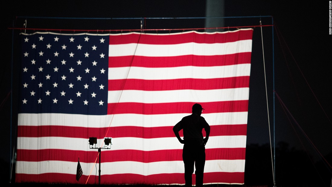 A man stands in front of a large American flag set up on the National Mall in Washington on May 27.