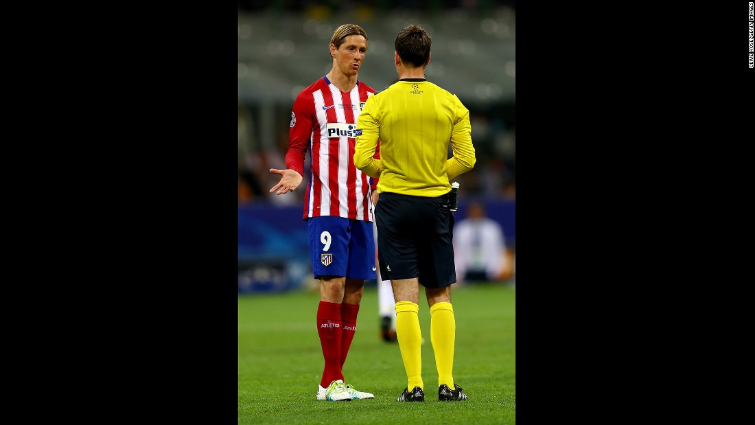 Fernando Torres of Atletico Madrid argues with referee Mark Clattenburg.