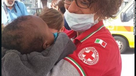 An Italian Red Cross worker holds a rescued baby who arrived in Messina, Italy. The baby was among more than 380 people on board a migrant boat.