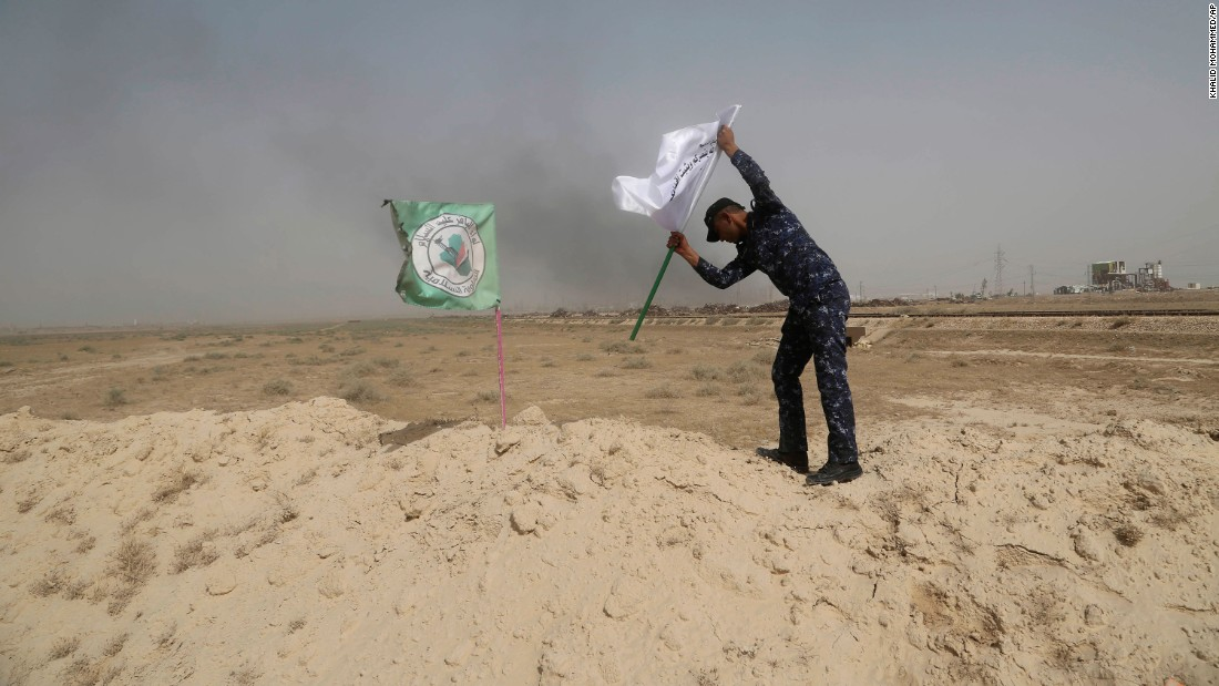 A police officer places an Iraqi federal police flag next to a Shiite militia flag outside Falluja on May 28.