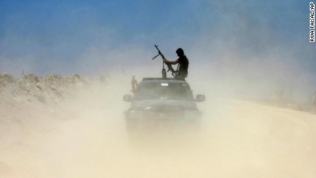A fighter from a Shiite militia takes a combat position outside Falluja on Monday, May 23.