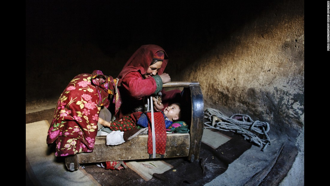 "A mother tends to her son inside their home in Afghanistan's <a href=""http://cnnphotos.blogs.cnn.com/2014/06/22/on-top-of-the-world-untouched-by-war/"" target=""_blank"">Wakhan Corridor</a> in October 2007."