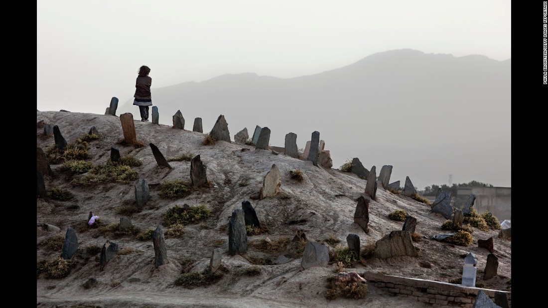 A girl stands on a cemetery hill after attending a funeral in Kabul in October 2009.