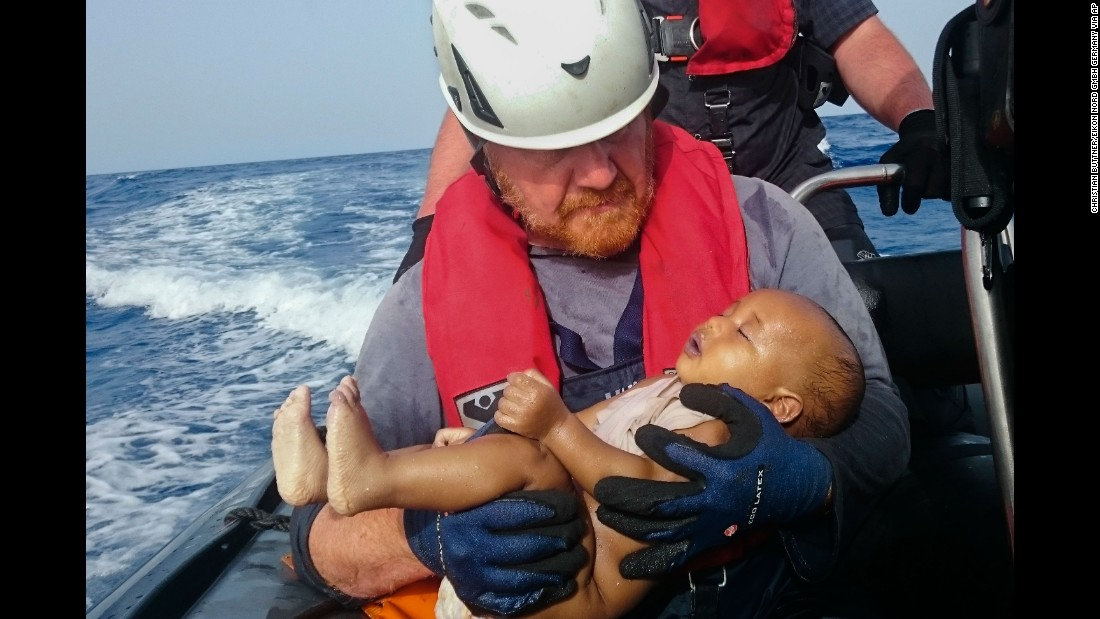 A member of the humanitarian organization Sea-Watch holds a migrant baby who drowned following the capsizing of a boat off Libya on Friday, May 27.