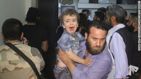 A man carries a crying child at a hospital following Russian air strikes that targeted many areas in Syria's northwestern city of Idlib early on May 31, 2016, according to the Syrian Observatory of Human Rights.
