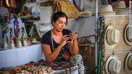 A woman uses her mobile phone to connect to internet via wi-fi in a street of Havana, on July 2, 2015. Cuban state-owned telecommunications company Etecsa opened 35 public Wi-Fi areas in the country and lowered the rate of connections to half the price in an effort to expand the limited connectivity on the island.      AFP PHOTO/YAMIL LAGE        (Photo credit should read YAMIL LAGE/AFP/Getty Images)