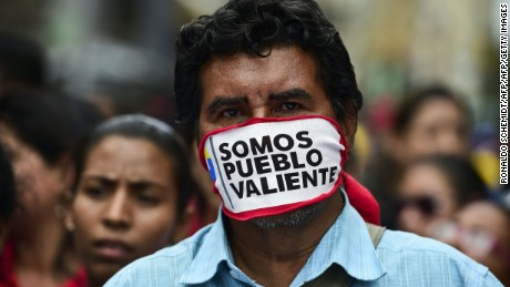 "Supporters of Venezuelan President Nicolas Maduro take part in a protest against the Organization of American States (OAS) and its Secretary General Luis Almagro, in Caracas, on June 01, 2016.  As part of an escalating war of words, Maduro on the eve told the head of the Washington-based organization to ""shove it."" The verbal barrage came after Almagro called for an urgent meeting on the Venezuelan crisis, warning democracy was at risk in the country.  / AFP / RONALDO SCHEMIDT        (Photo credit should read RONALDO SCHEMIDT/AFP/Getty Images)"