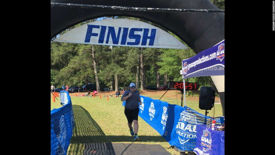 """Crossing the finish line at the Tall Pines Sprint Triathlon, some 100 pounds lighter than six months before."""