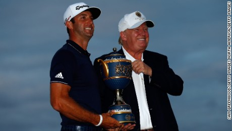 Winner Dustin Johnson and course owner Donald Trump pose with the Gene Sarazen Cup after Johnson's 29015 win at the World Golf Championships-Cadillac Championship at Trump National Doral on March 8, 2015. The event will be relocated from 2017.