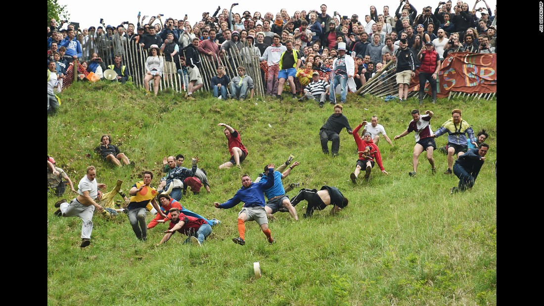People compete Monday, May 30, in the annual cheese-rolling races at Cooper's Hill in Brockworth, England. In the races, which date to the early 1800s, runners chase cheese wheels down an extremely steep hill. The first person over the finish line in each race wins the cheese.