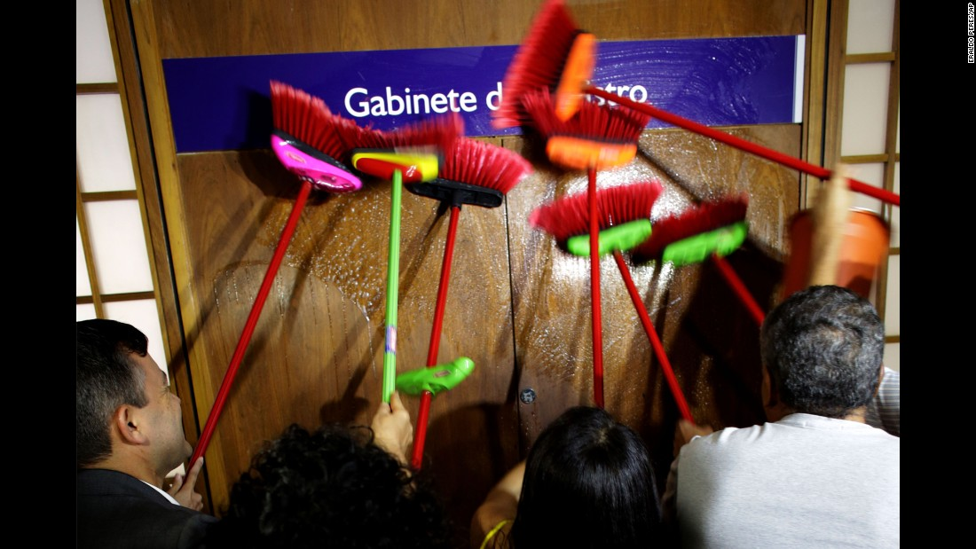 """Ministerial staff members use brooms to scrub the office door of Brazilian Transparency Minister Fabiano Silveira, demanding his resignation on Monday, May 30. The day before, <a href=""""http://money.cnn.com/2016/06/01/news/economy/brazil-recession-economy/"""" target=""""_blank"""">leaked phone call recordings</a> showed Silveira -- who was appointed to combat corruption -- advising a senator on how to dodge a corruption probe. Silveira resigned Monday. Protesters in Brazil use brooms as a symbol to sweep away corruption."""