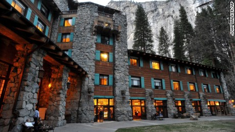 File - In this March 24, 2014 file photo, the historic Ahwahnee Hotel is lit up as dusk falls over Yosemite National Park, Calif. A new concessionaire takes over Tuesday at the park and many of the landmark places will have name changes at least temporarily because the old concessionaire lays claim to the names. The famed Ahwahnee Hotel is set to become the Majestic Yosemite Hotel. (John Walker/Fresno Bee via AP, File)