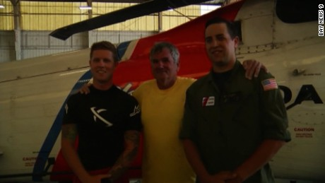 William Durden, center, with Coast Guard rescuers after being pulled from Gulf of Mexico