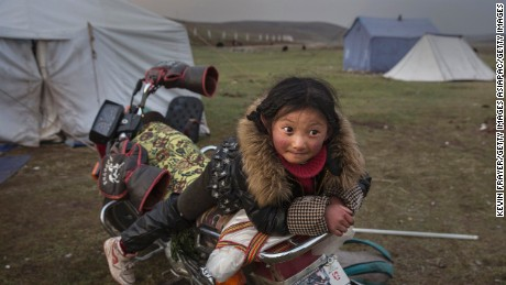 A Tibetan nomad girl rests on a motorcycle  at a temporary camp for picking cordycep fungus on May 22, 2016.