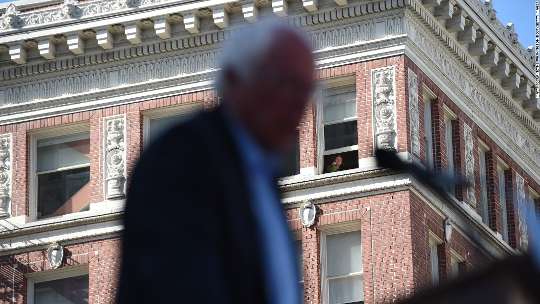 A person watches from a window as U.S. Sen. Bernie Sanders speaks at a presidential campaign rally in Oakland, California, on Monday, May 30.