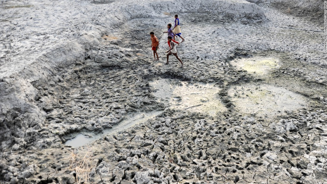 Children walk through the parched mud of the dried-up Varuna River in Phoolpur, India, on Saturday, May 14. Much of India is reeling from a heat wave and severe drought conditions.