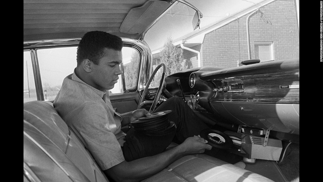 Cassius Clay plays a record in his 1960 Cadillac outside of his home in 1960.