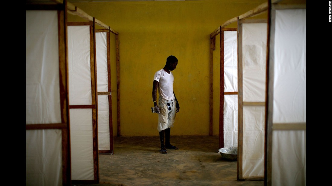 At the height of the Ebola epidemic, a worker puts the finishing touches on dividers that will separate patients at a community care center in Sierra Leone's Port Loko District.
