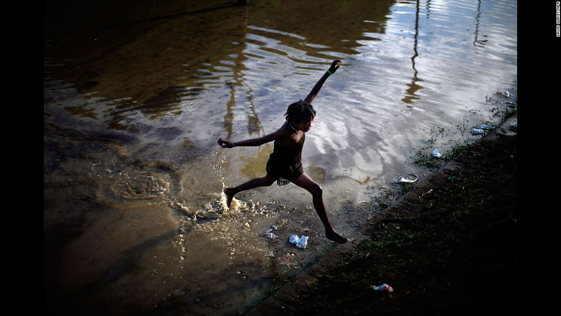 A little girl jumps across a flooded field that contains sewage runoff from a camp in Port-au-Prince, Haiti, in 2010.