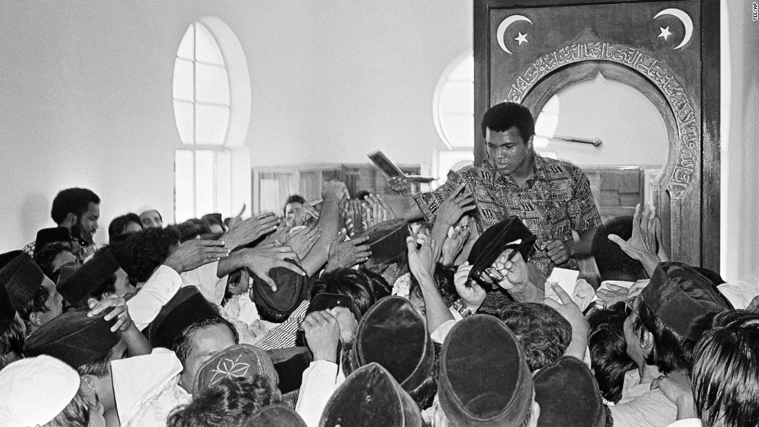 Muslims reach out to shake hands with Muhammad Ali during his visit to a mosque in Kuala Lumpur, Malaysia, in June 1975. After leaving the Nation of Islam, Ali followed Sunni Islam.