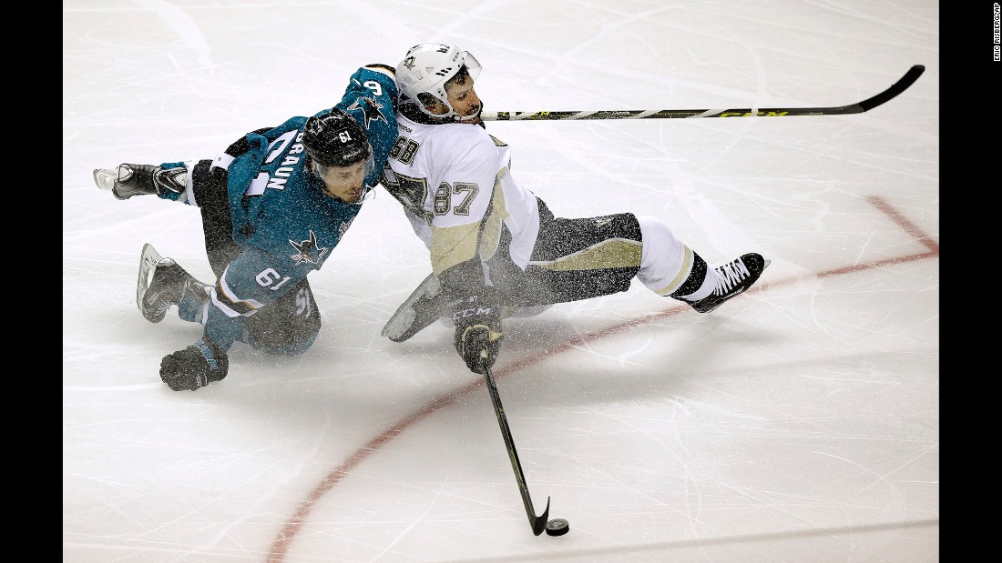 Pittsburgh center Sidney Crosby reaches for the puck in front of San Jose defenseman Justin Braun during Game 3 of the NHL's Stanley Cup Final on Saturday, June 4.