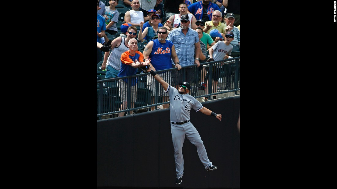 A baseball fan in New York reaches out for the same ball that Chicago White Sox outfielder Melky Cabrera was trying to catch on Wednesday, June 1. The play was ruled an out after video review.