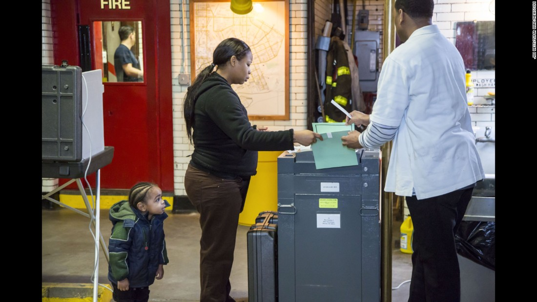 A boy watches his mother vote at a fire station in Detroit on Tuesday, March 8.