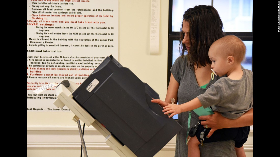 Kisha Raybor holds her 1-year-old son, Kullen, as she votes in Hattiesburg, Mississippi, on Tuesday, March 8.