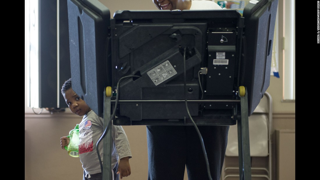 A child peeks around a voting booth in Ferguson, Missouri, on Tuesday, March 15.