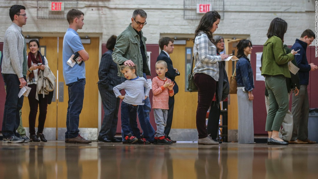 Steve Amos watches his sons, Cy, left, and Leon as he waits in line to vote Tuesday, March 1, in Atlanta.