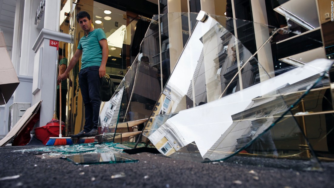 A man cleans debris outside his shop near the scene of the blast.