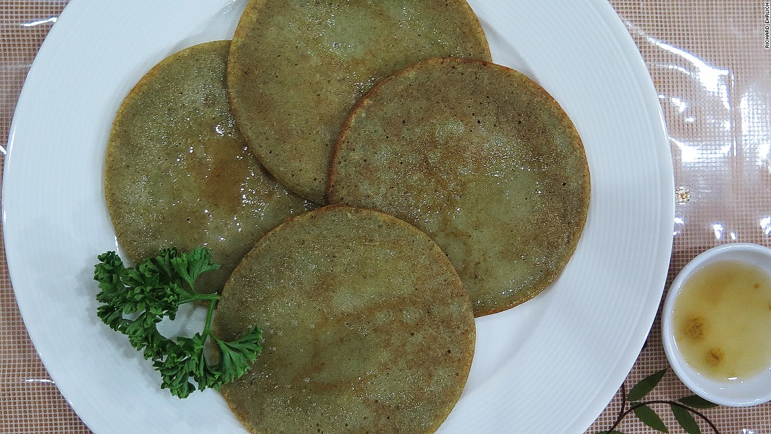 Mung Bean Jijim features four flat, thin, green, circular pancakes, wet with oil and adorned with parsley.