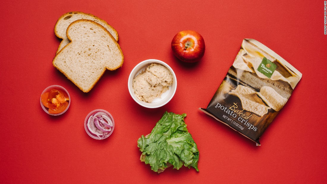 Healthy food that's easy to eat while driving is found in the tuna salad sandwich on honey wheat with apple and baked crisps.
